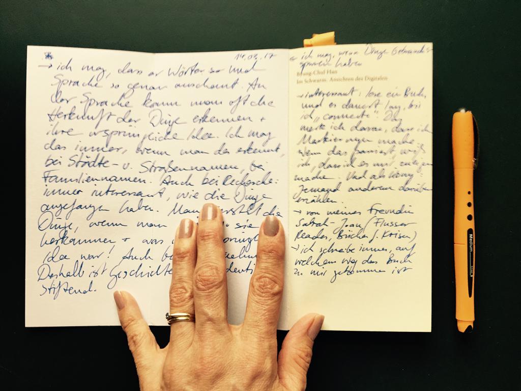 Julia hält mit ihrer Hand ein Buch auf. Man sieht Notizen im Buch.