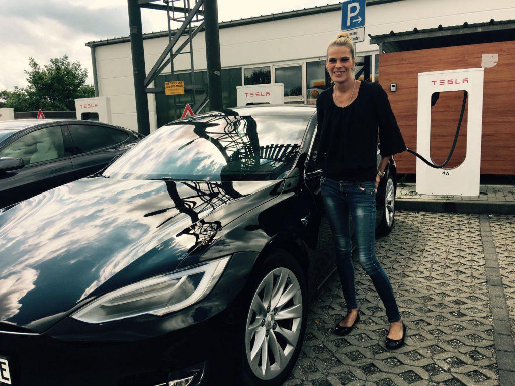 Frau vor Tesla Ladestation