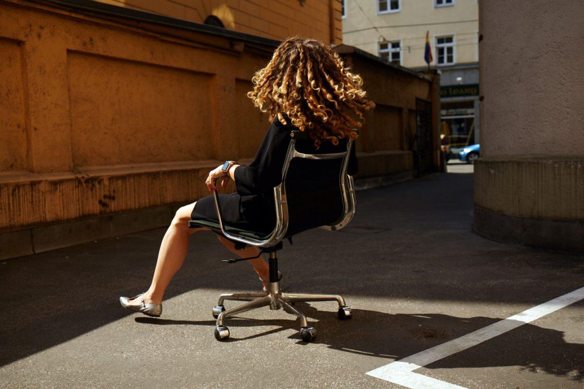 Die digitale Nomadin rollt mit ihrem Bürostuhl im Hinterhof herum