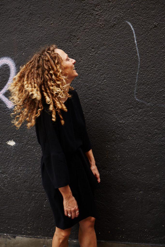 Julia lacht vor einer grauen Wand – die Locken fliegen