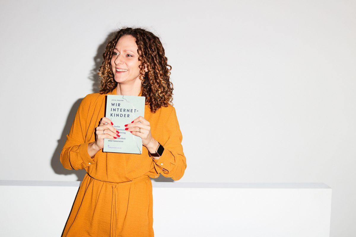 """Julia hält ihr Buch """"Wir Internetkinder"""" in die Kamera"""